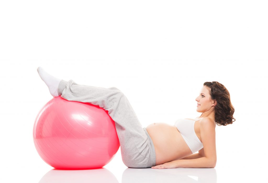A pregnant woman training with a fitness ball on white