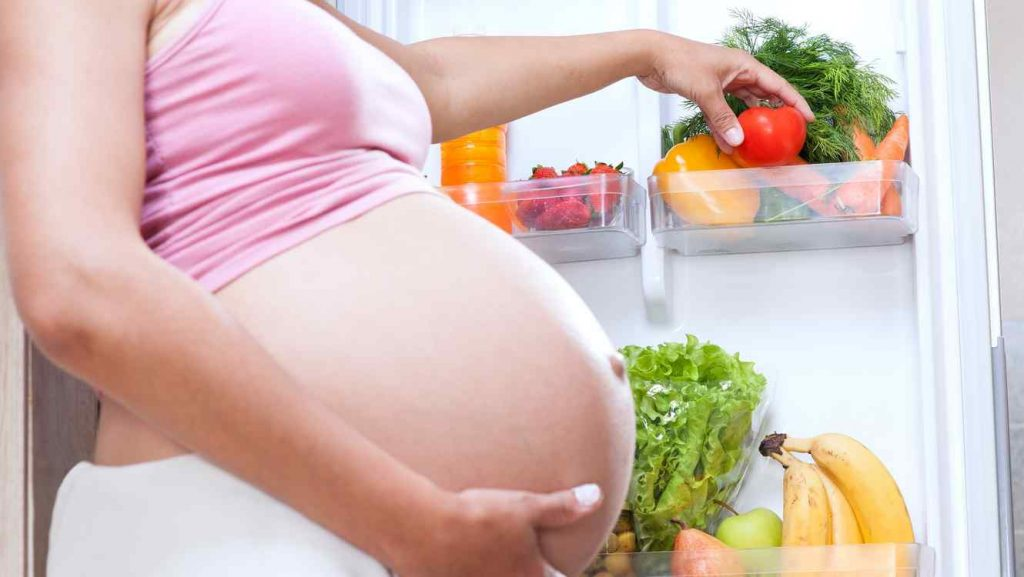 mujer-embarazada-escogiendo-un-tomate-del-refrigerador